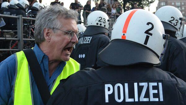 Участник акции протеста (слева) в преддверии саммита G20 в Гамбурге