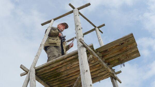 Начальник экспедиции Виктор Андрианов ведет наблюдения за стадом белух с наблюдательной вышки с берега Онежского залива в районе мыса Глубокий