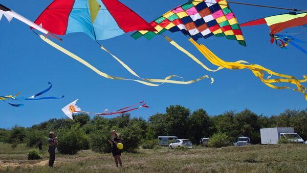 Девушки запускает воздушного змея на фестивале Пирфест в окрестностях Красных пещер у села Перевальное