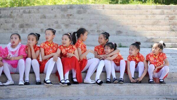 Дети ожидают начала своего выступления на школьном празднике в Маньчжурии