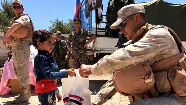 Военнослужащие российского центра по примирению враждующих сторон раздают гуманитарную помощь в Сирии. Архивное фото