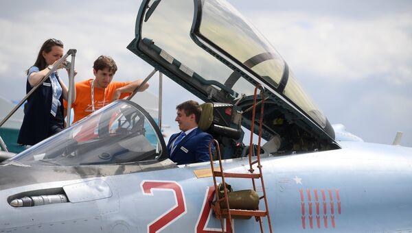 Участники Международного авиационно-космического салона МАКС-2017 в подмосковном Жуковском осматривают кабину самолета СУ-35