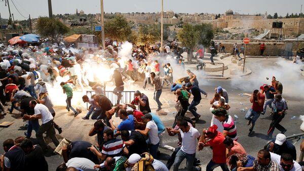 Палестинцы бегут от слезоточивого газа, распыленного израильскими военными после пятничной молитвы на улице за пределами старого города Иерусалима. 21 июля 2017