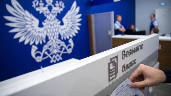 Посетитель берет бланк в отделении Почты России