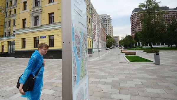 Молодой человек у информационной доски на Якиманской набережной в Москве. 11 августа 2017