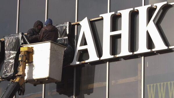Рабочие завешивают вывеску с названием банка в Москве. Архивное фото