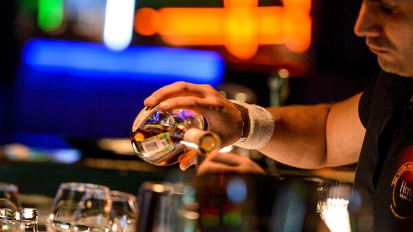 Бармен разливает напитки за барной стойкой