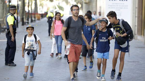 Люди на месте наезда микроавтобуса на пешеходов в Барселоне. 17 августа 2017