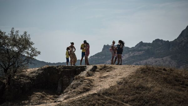 Отдыхающие гуляют недалеко от пляжа в Коктебеле