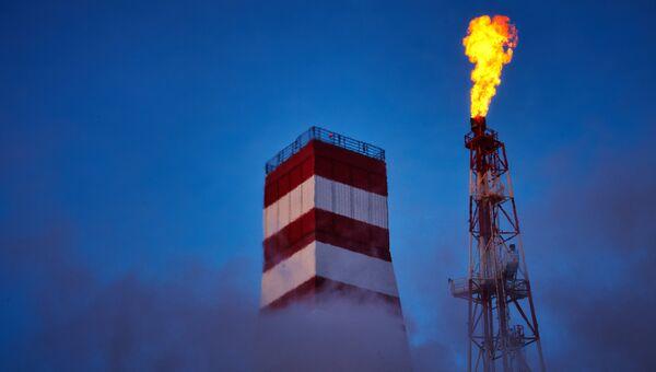 Буровая вышка и газовый факел морской нефтеперерабатывающей платформы. Архивное фото