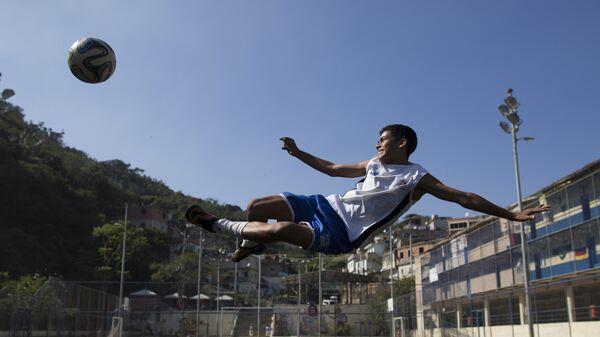 Мальчик играет в футбол в трущобах Vidigal Рио-де-Жанейро, Бразилия. 17 июня 2014 год