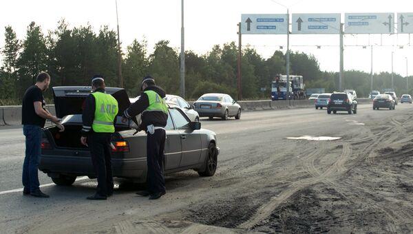 Сотрудники дорожно-патрульной службы проверяют легковой автомобиль, выезжающий из города Сургута. 19 августа 2017