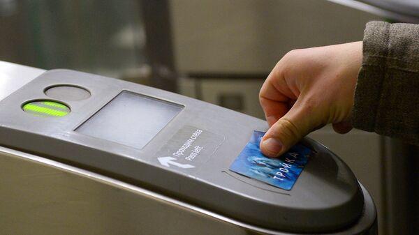 Пассажир оплачивает проезд у турникета в метро