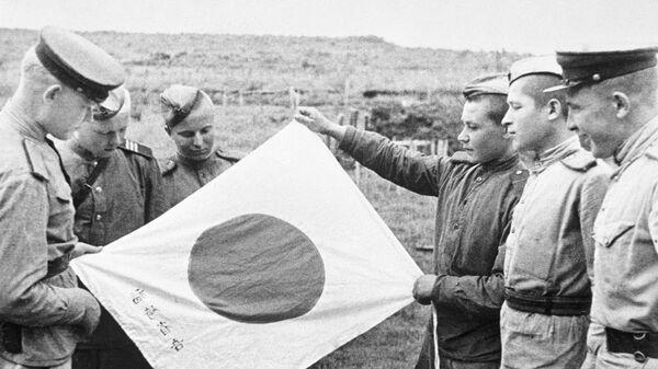 Советские воины рассматривают брошенный при отступлении японский флаг. Архивное фото