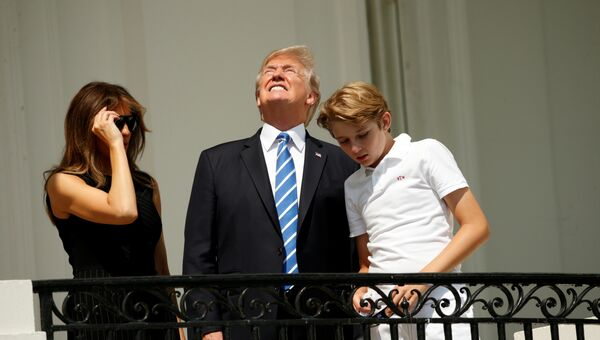 Президент США Дональд Трамп с семьей наблюдают за солнечным затмением с балкона Белого дома. 21 августа 2017