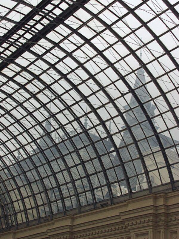 Сквозь стеклянные потолочные своды здания Государственного универсального магазина (ГУМ), расположенного на Красной площади в Москве, видны башни Кремля.