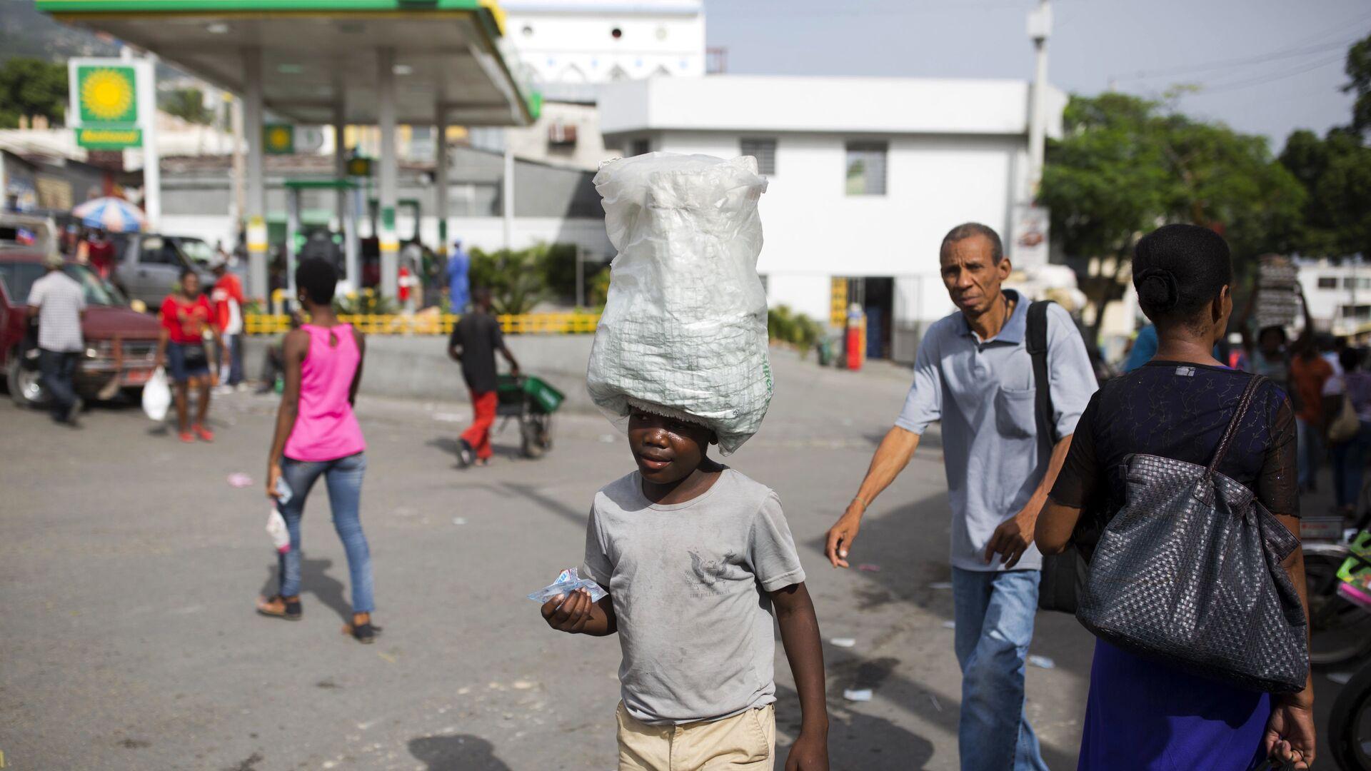 12-летний мальчик носит воду, предназначенную для продажи, по улицам Порт-о-Пренс, Гаити - РИА Новости, 1920, 27.02.2020