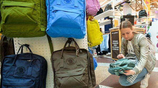 Женщина выбирает рюкзак для своего ребенка к началу учебного года на школьной ярмарке в Центральном детском магазине. Архивное фото