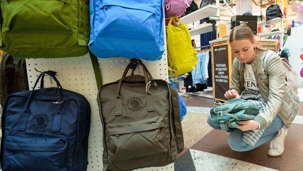 Женщина выбирает рюкзак для своего ребенка. Архивное фото