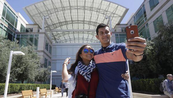 Посетители делают селфи перед штаб-квартирой компании Apple в Купертино, Калифорния