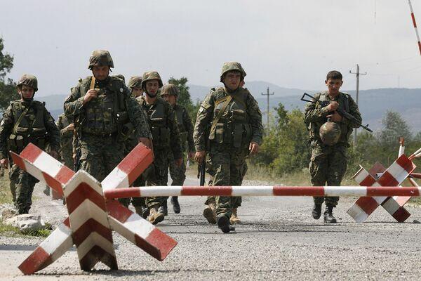 Грузинские солдаты пересекают блокпост миротворческих сил в Южной Осетии