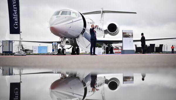 Посетитель у самолета Gulfstream G650ER на международной выставке деловой авиации JetExpo 2017