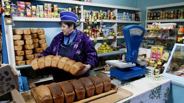 Продавец принимает свежий хлеб в сельском магазине