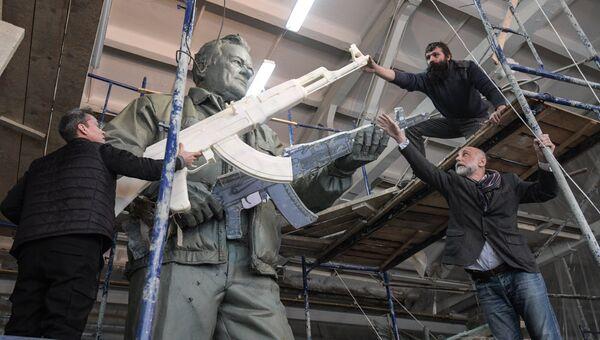 Скульптор Салават Щербаков (справа) в своей мастерской у памятника конструктору стрелкового оружия Михаилу Калашникову