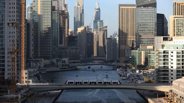 Трамвай проезжает по мосту через канал в Дубае