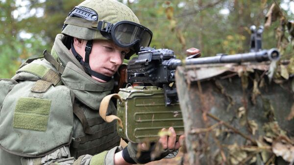 Военнослужащий во время учений вооружённых сил России и Белоруссии на Лужском полигоне в Ленинградской области с пулеметом Калашникова