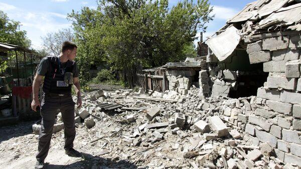 Сотрудник ОБСЕ осматривает двор жилого дома, пострадавший в результате обстрела. Архивное фото