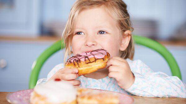 Девочка ест пончики