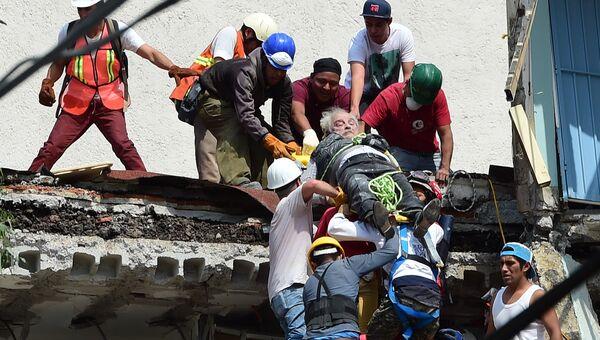 Спасатели вытаскивают пострадавшего из под завалов после землетрясения в Мехико. 19 сентября 2017