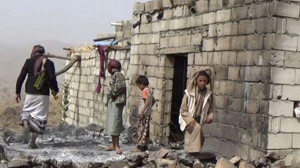 Местные жители осматривают разрушенный дом после авиаударов по селу Якла в Йемене. Архивное фото