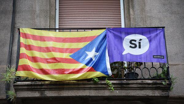 Агитационный плакат и флаг на одном из балконов в Барселоне, где проходил референдум о независимости Каталонии от Испании. 1 октября 2017