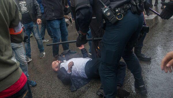 Сотрудники полиции задерживают участников столкновений у избирательных участков в ходе референдума о независимости Каталонии. 1 октября 2017