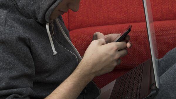 Молодой человек переписывается в телефоне. Архивное фото