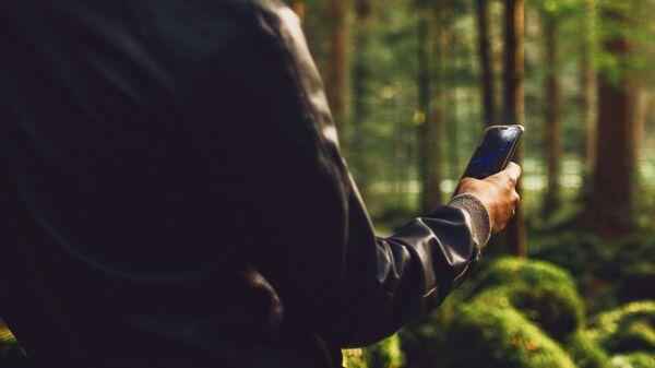 Молодой человек в лесу с телефоном