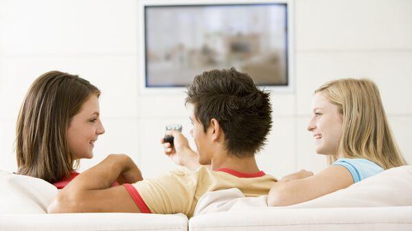 Молодые люди смотрят телевизор. Архивное фото