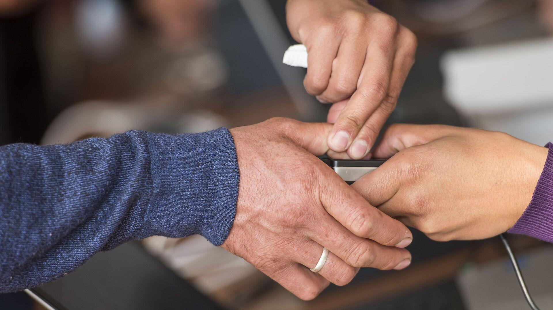 Сканирование отпечатка пальца избирателя на избирательном участке в Бишкеке в ходе выборов президента Киргизии. 15 октября 2017 - РИА Новости, 1920, 13.08.2020