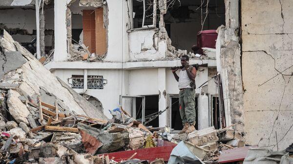 Сомалийский солдат стоит на месте взрыва в центре Могадишо. 15 октября 2017