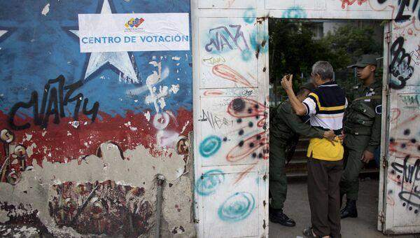 Досмотр жителя Каракаса перед входом на избирательный участок