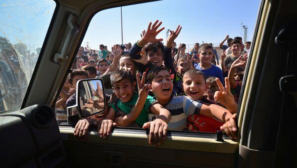 Дети приветствуют автомобили членов служб безопасности Ирака в Киркуке