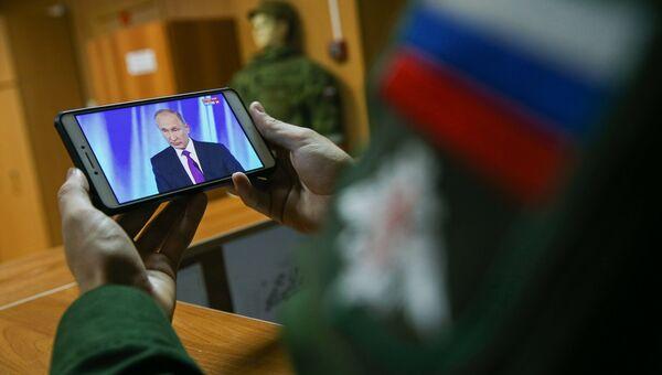 Военнослужащий смотрит трансляцию выступления президента РФ Владимира Путина на заседании клуба Валдай