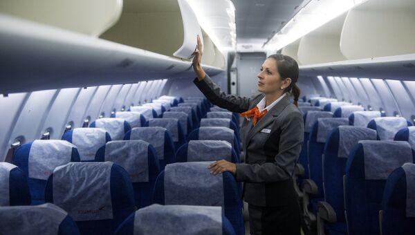 Стюардесса в салоне самолета. Архивное фото