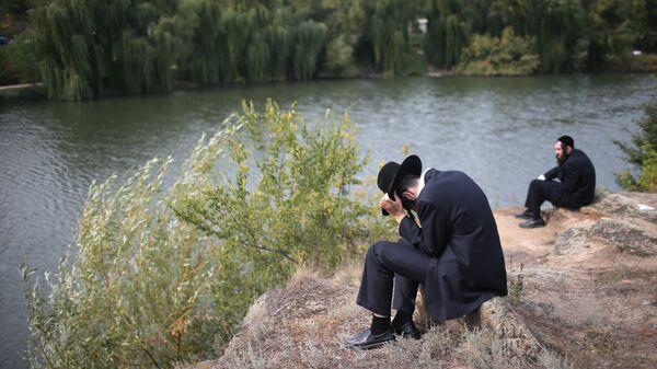 Паломник сидит на берегу реки в канун еврейского нового года на Украине