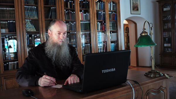 Священнослужитель за компьютером в библиотеке Свято-Троицкой Сергиевой Лавры