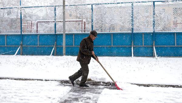 Мужчина убирает снег во дворе жилого дома. Архивное фото