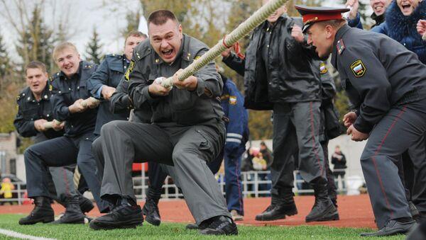 Сотрудники полиции участвуют в перетягивании каната во время спортивного праздника, посвященного Дню сотрудников органов внутренних дел в Великом Новгороде