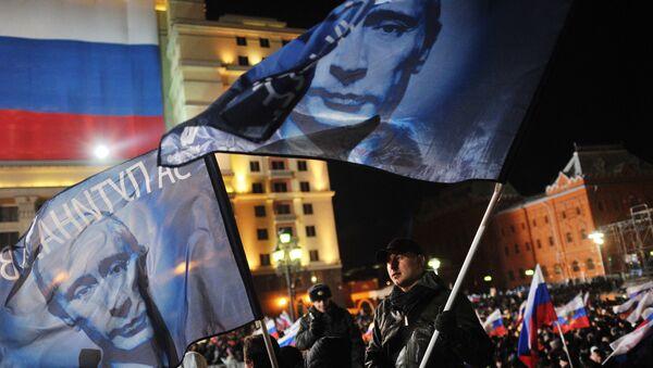 Участники санкционированного митинга в поддержку кандидата в президента РФ Владимира Путина на Манежной площади